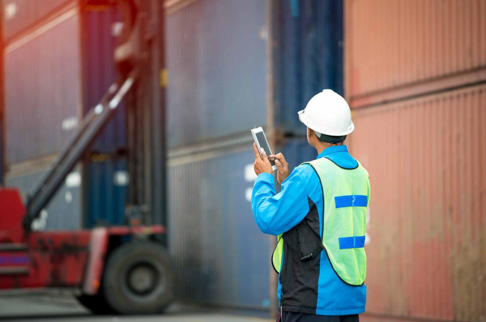 Een havenarbeider bedient een mobiel toestel